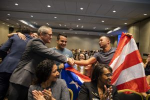 Dr. Whittaker shaking hands with student holding Puerto Rican flag
